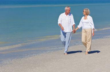 Idosos caminhando na praia, Mar17